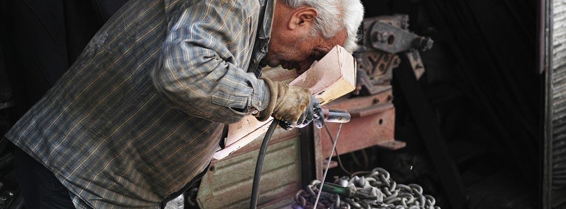 Hombre con pelo blanco realizando trabajo de soldadura