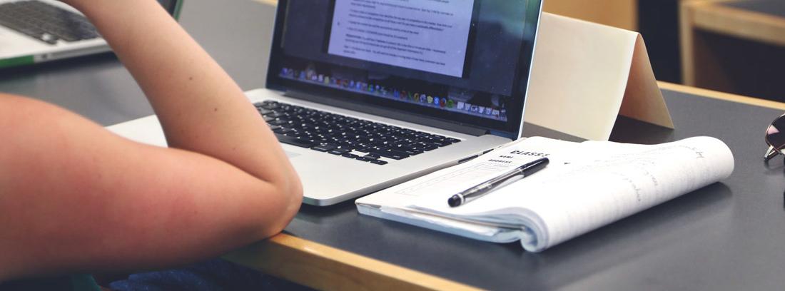 Persona apoyada en una mesa con ordenador, cuaderno y boli