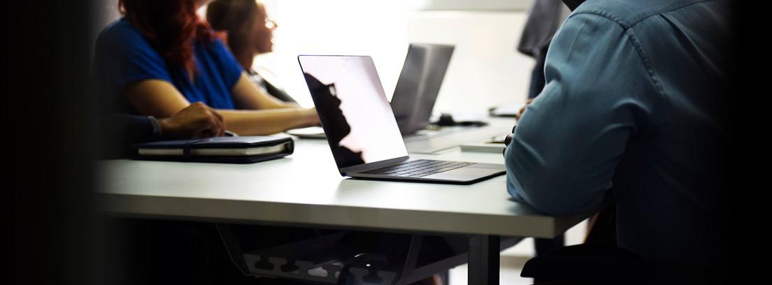 Grupo de personas con portátiles y siguiendo un curso en pantalla