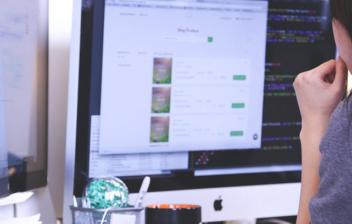 Persona delante de una pantalla de ordenador en escritorio de trabajo