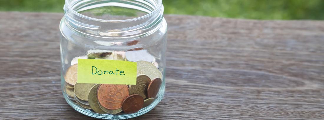 bote con monedas y una etiqueta que pone donativo