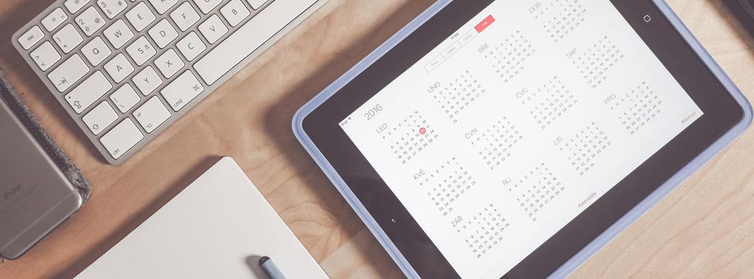 Vista cenital de una mesa con un teclado, un cuaderno y un calendario en el que apuntar los días de asuntos propios