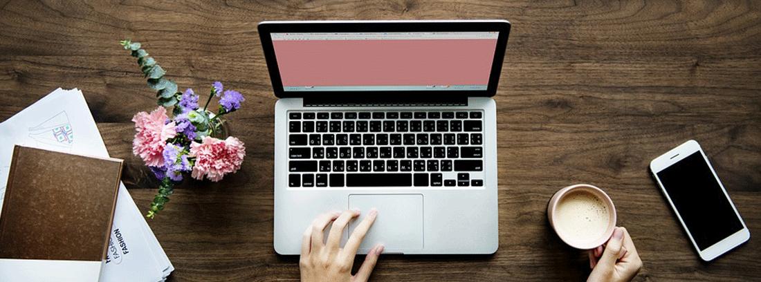 mujer sosteniendo una taza de café frente a un ordenador