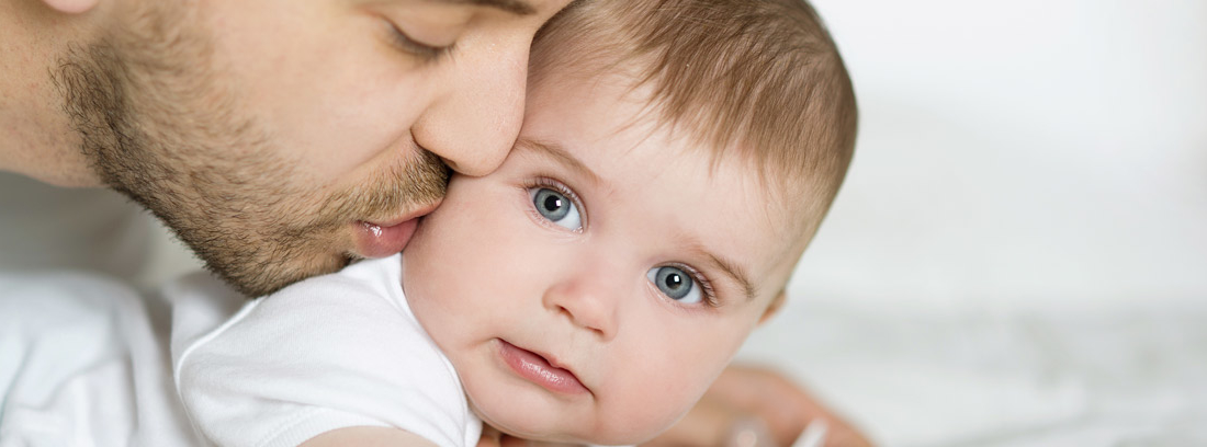 Hombre dando un beso a un bebé durante una excedencia por cuidado de hijos