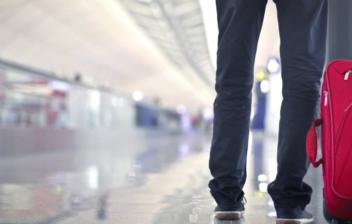 Vista parcial de un hombre tirando de una maleta en una estación de transporte