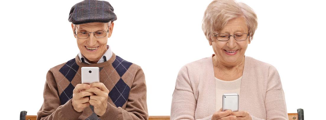 dos ancianos sentados en un banco con sus teléfonos móviles