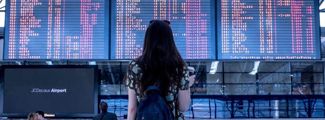 Mujer delante de un panel luminoso informativos sobre destinos de viaje
