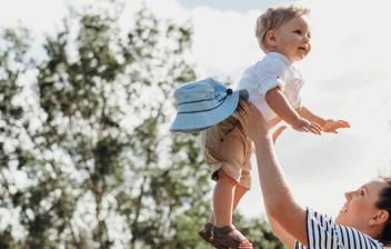 Mujer sujeta en el aire por la cintura un niño pequeño
