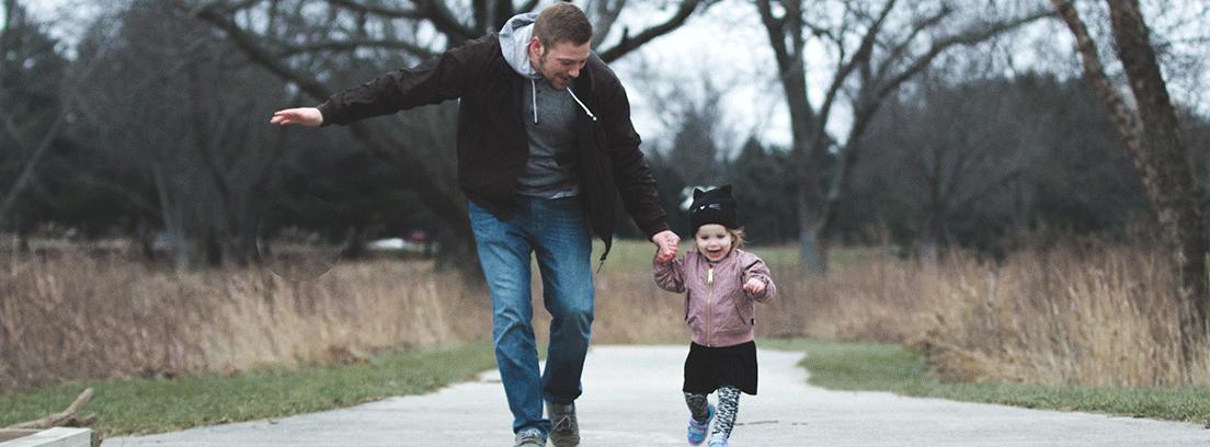 Hombre y niña pequeña corriendo de la mano
