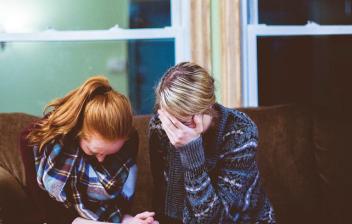 Dos mujeres de la mano, llorando y sentadas en un sillón