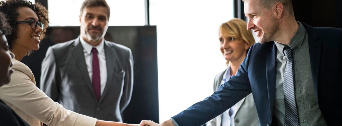 Hombre y mujer se estrechan la mano en señal de acuerdo