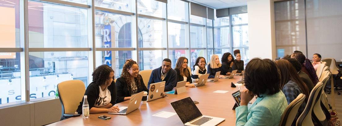 Grupo de personas con portátiles sentados en una gran mesa de trabajo