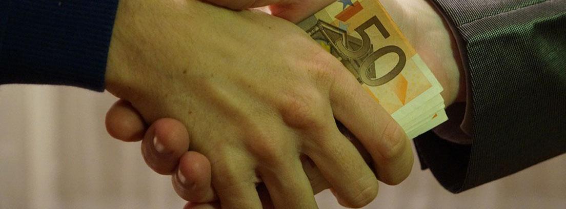 dos manos se pasan un billete de 50 euros