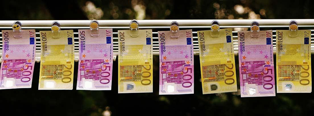 Billetes de euro colgados con pinzas de una cuerda