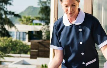 mujer con uniforme recogiendo una terraza