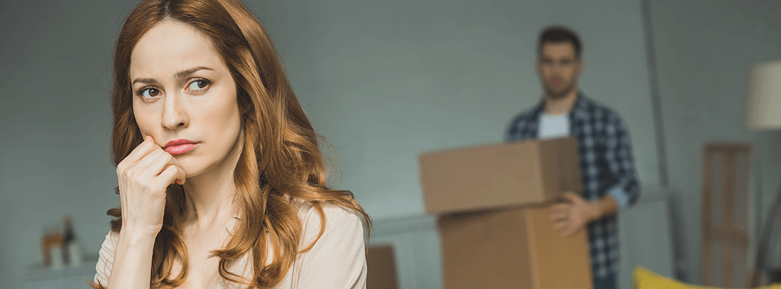 mujer pensativa y hombre al fondo con cajas de mudanza