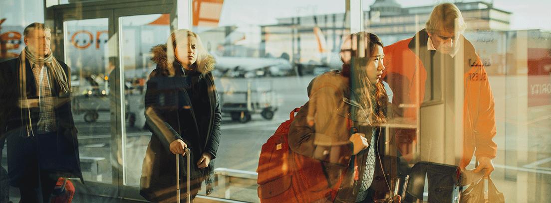 Varias personas con maletas en un aeropuerto