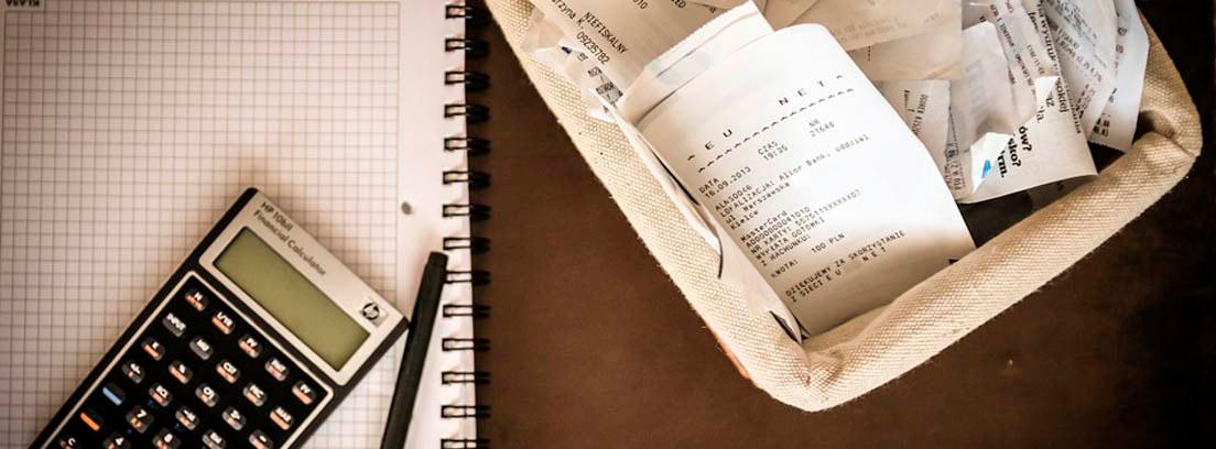 Calculadora sobre un cuaderno y cesta con facturas