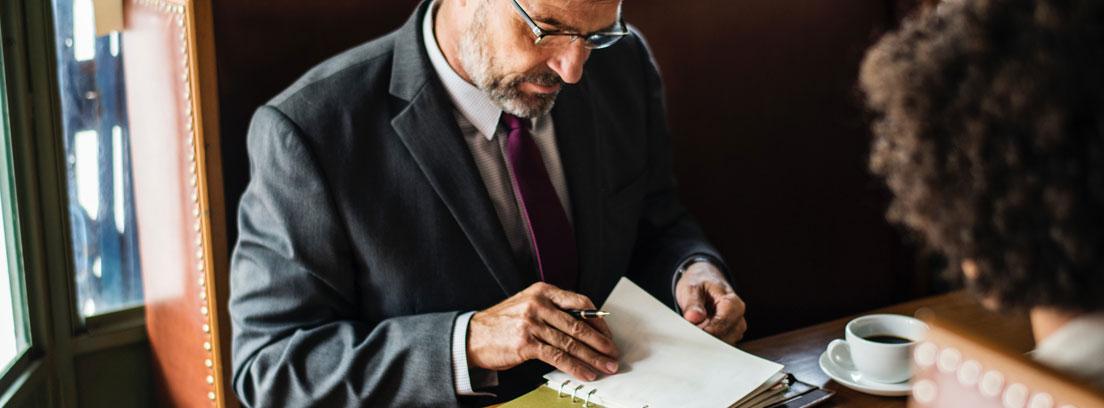 Hombre con agenda laboral sobre la mesa frente a otra persona
