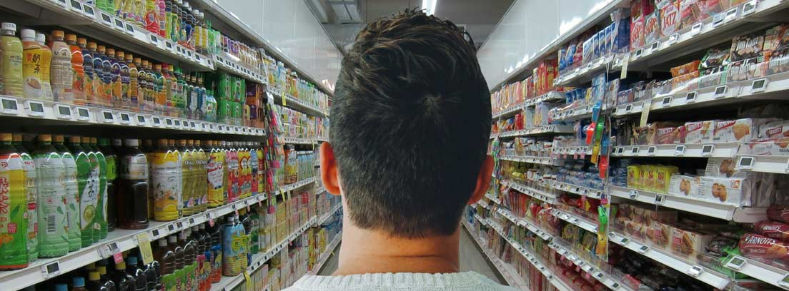 Hombre de espaldas buscando productos de temporada en un pasillo de un supermercado