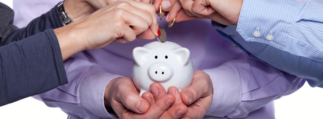 Varias personas metiendo monedas en una hucha para ahorrar en la comunidad de vecinos