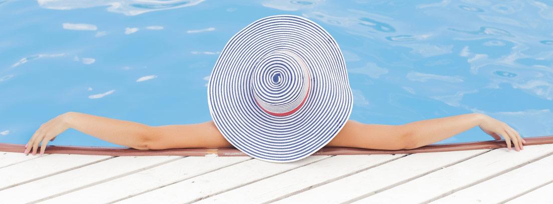 Mujer de espaldas con pamela metida en una piscina