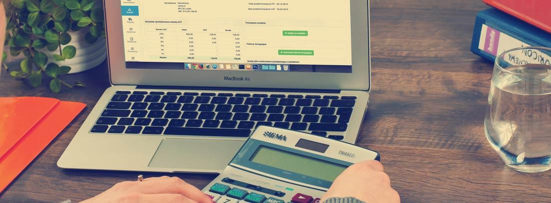 Mujer con ordenador y calculadora mirando varios presupuestos para ahorrar en la comunidad de vecinos