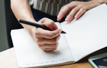 Persona anotando gastos en un cuaderno