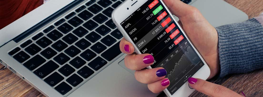 Mano delante de teclado portátil con un móvil con gastos apuntados