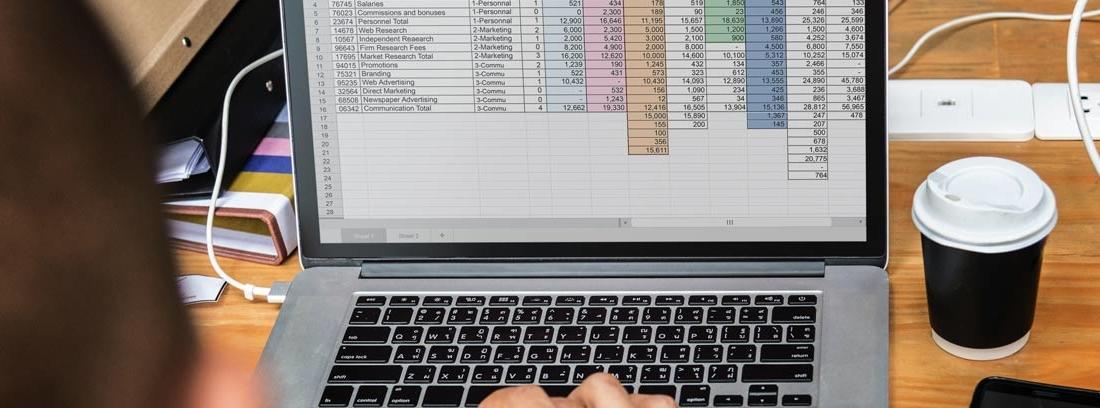 Persona delante del ordenador gestionando Excel con inventario