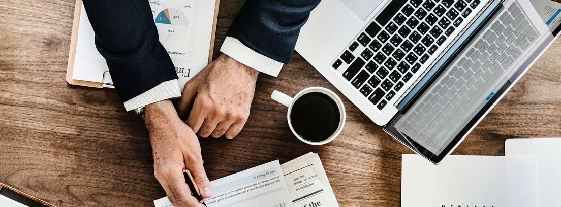 Vista cenital de un hombre sobre una mesa con un ordenador, calendario y agenda señalando un gráfico