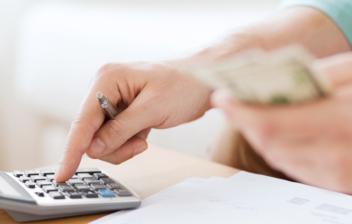 Vista de una manos con billetes y una calculadora calculando su aportación máxima al plan de pensiones