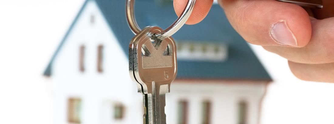 Casa de fondo con unas llaves en primer plano