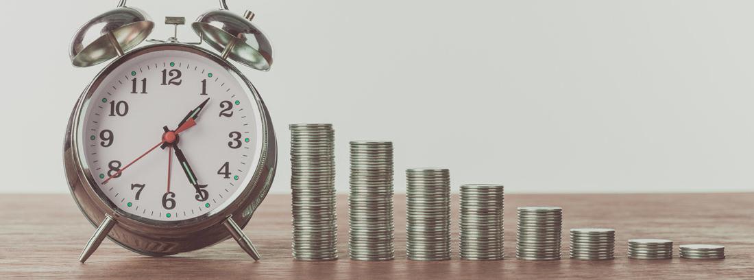 Reloj despertador y varias columnas de monedas en sentido decreciente