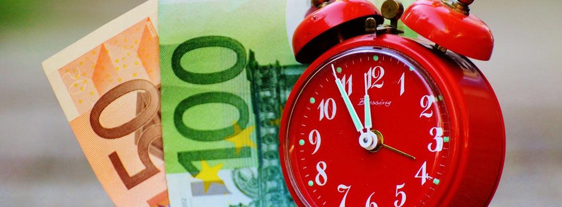Billetes de 50 y 100 euros detrás de un reloj rojo