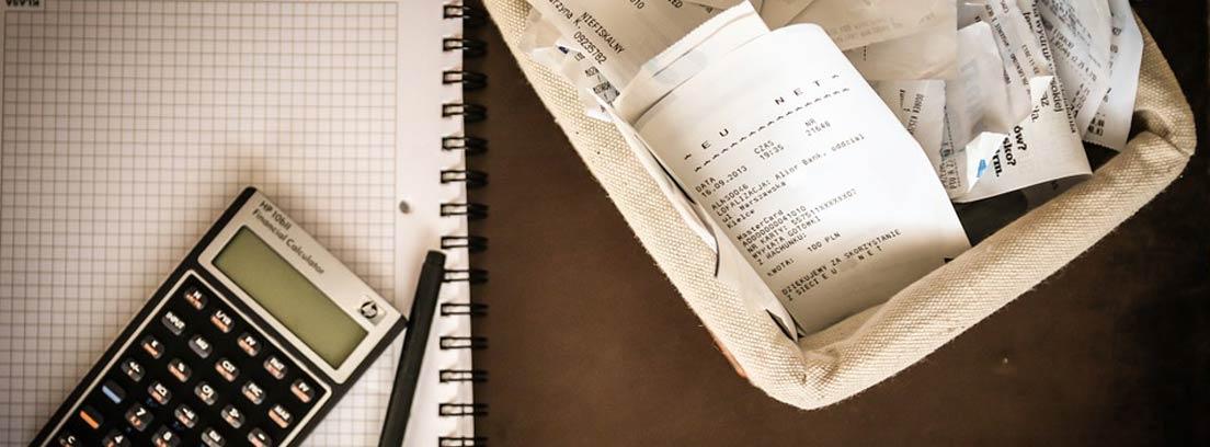 calculadora, cuaderno y cesta llena de tickets