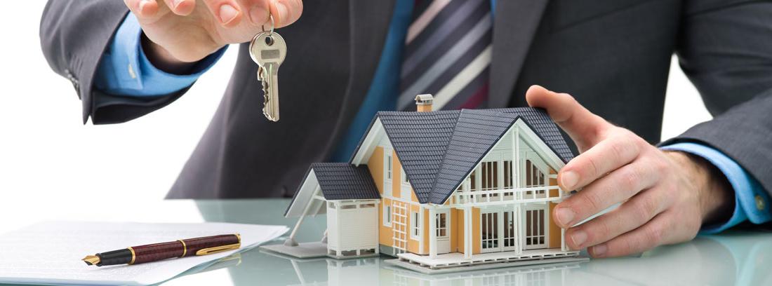Hombre con una maqueta de una casa, unas llaves y unos documentos con las condiciones de la hipoteca