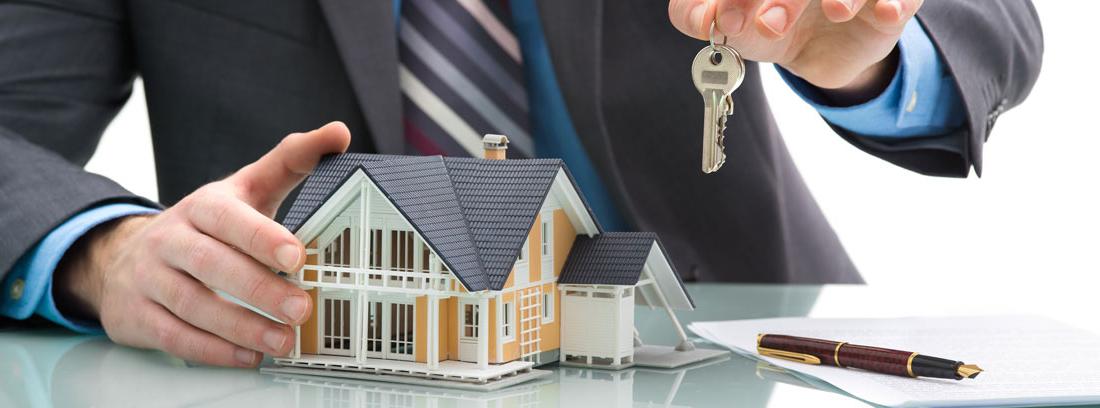 Hombre con una maqueta de una casa, unas llaves y unos documentos