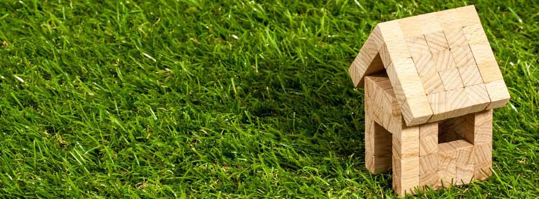 Casa de juguete de madera sobre hierba