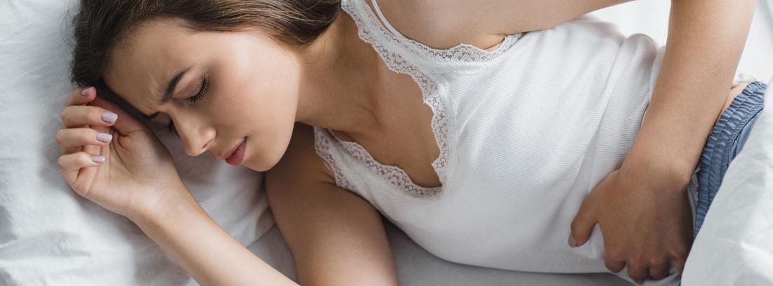 Mujer en la cama con dolor abdominal