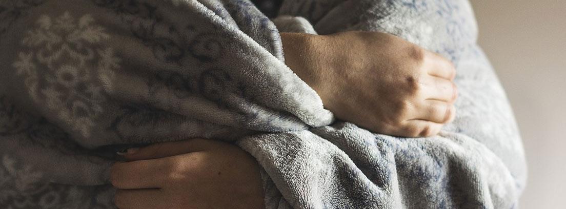 Mujer arropada con una manta gris