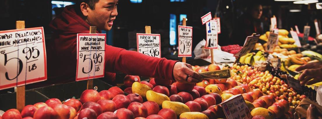 Puesto de fruta en un mercado con persona devolviendo dinero a cliente