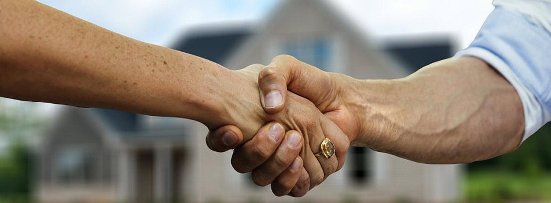Dos personas dándose un apretón de manos frente a una vivienda