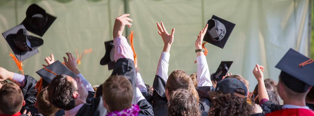 Estudiantes con togas y birretes lanzados al aire