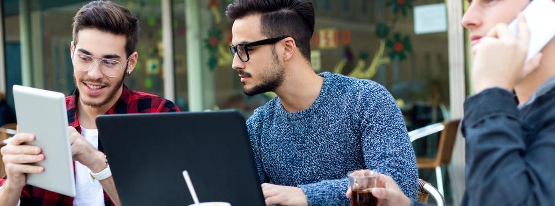 Tres trabajadores autónomos en la mesa de un bar con un ordenador, una tablet y un teléfono móvil