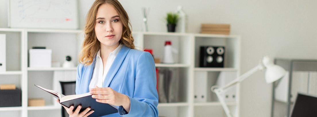 Mujer con traje azul y un libro de pie junto a una mesa
