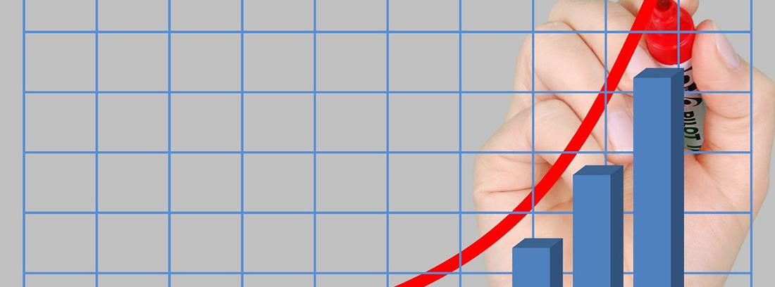 Mano pintando una línea roja sobre gráfico de barras.