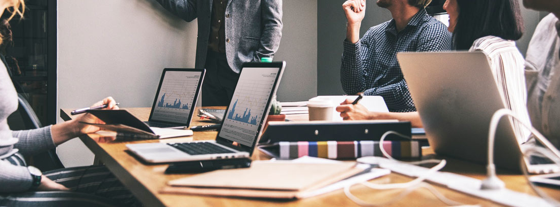 Varias personas en mesa de trabajo planeando estrategia de benchmark