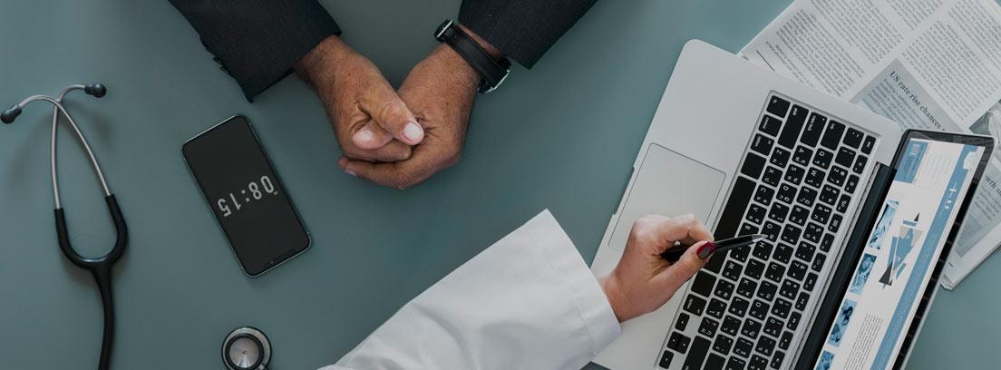 Vista cenital de un médico con un ordenador y un fonendoscopio y un enfermo con incapacidad temporal