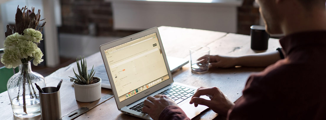 Hombre tecleando sobre ordenador portátil